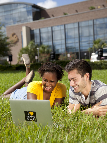 Students on a lawn with a laptop