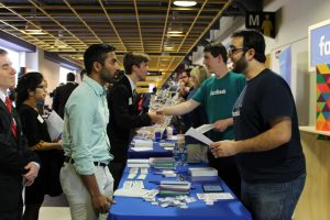 recruiter chatting with student at career fair