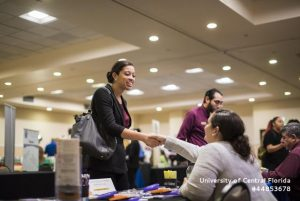 student shakes a recruiter's hand at a career fair
